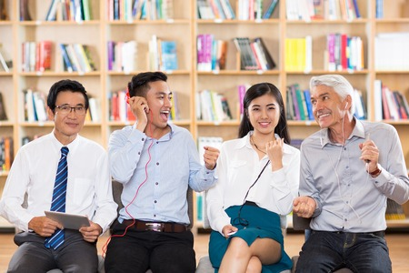 two people with others: Hilarious business people resting after work in library. Senior Asian man with gadget looking at camera, others listening to music on mp3 players. Two managers dancing. Leisure concept