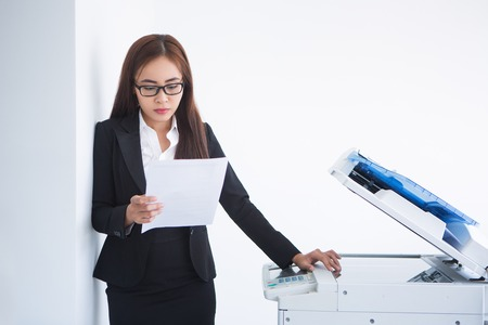 Closeup of serious Asian business woman leaning on wall, reading document and standing at copier machine. Isolated view on white background.