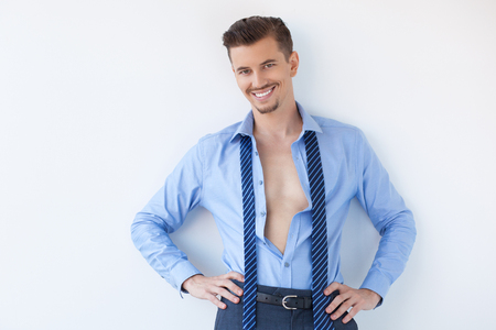 Closeup of smiling young handsome business man looking at camera, wearing unbuttoned shirt and standing with hands on hips. Isolated view on white background.