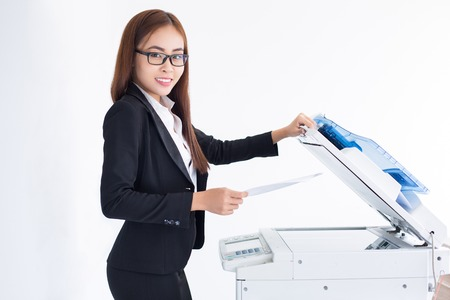 Closeup of smiling at camera Asian business woman using copier machine. Isolated view on white background.