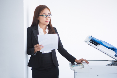 thinking machines: Closeup of pensive Asian business woman leaning on wall, looking away, thinking, holding document and standing at copier machine. Isolated view on white background.