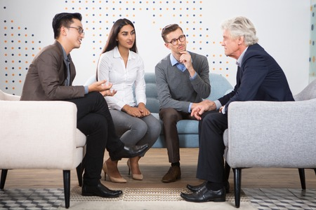 couching: Interested young people talking to senior business leader. They are sitting in armchairs and sofa in lounge. Stock Photo