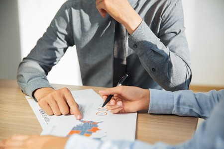 Unrecognizable business people sitting at table in office and discussing financial report. Businessman wearing grey shirt pointing at document and businesswoman holding ballpoint pen