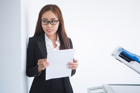 thinking machines: Closeup of Asian business woman looking away, holding document and standing at copier machine. Isolated view on white background.