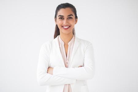 Close-upportret van glimlachende jonge aardige Indische bedrijfsvrouw die camera bekijken en zich met gekruiste wapens bevinden. Geïsoleerd vooraanzicht op witte achtergrond.