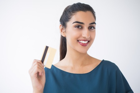 Closeup portrait of smiling young pretty Indian woman showing credit card. Isolated view on white background.