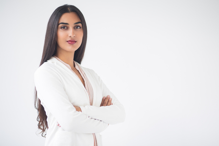 Closeup portrait of serious young gorgeous Indian business woman looking at camera and standing with arms crossed. Isolated view on white background. Stock Photo