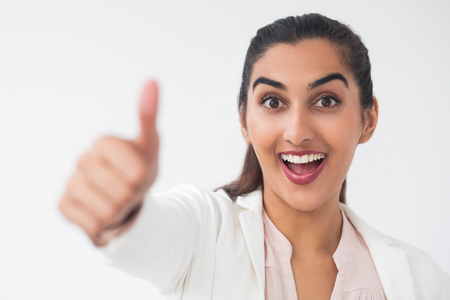 Closeup portrait of cheerful young pretty Indian business woman looking at camera and showing thumb up. Isolated view on white background.