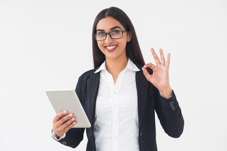 Closeup portrait of smiling young elegant Indian business woman looking at camera, holding tablet computer and showing OK sign. Isolated view on white background.