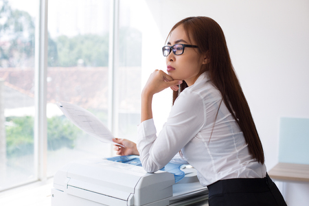 fotocopiadora: Closeup of thoughtful Asian business woman leaning on photocopier, holding document and looking nowhere with office window and blurred city view outside. Side view. Foto de archivo