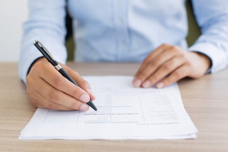 Cropped view of person holding pen and filling out application form on table