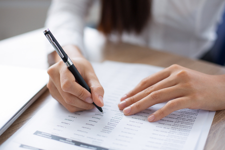 Cropped view of person holding pen and looking through document at desk