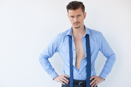 Closeup of disappointed young handsome business man looking at camera, frowning, wearing unbuttoned shirt and standing with hands on hips. Isolated view on white background. Stock Photo