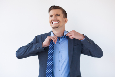 Angry young businessman untying or loosening necktie. Furious male manager nervous about business. Tired man undressing. Negative emotion concept