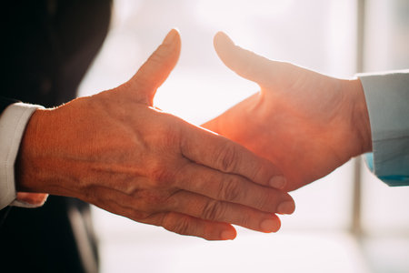 personas saludandose: Close-up of business partners reaching hands to shake it in sunlight. Unrecognizable people concluding successful deal or signing agreement. They greeting each other. Business relationship concept