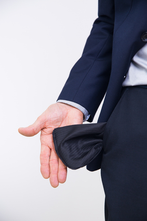 Close-up of hand of senior businessman in suit turning pocket of his trousers inside out and showing it empty. Crisis, unemployment, bankruptcy concept Stock Photo