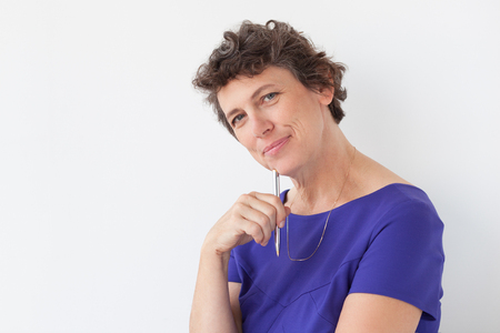 mujeres morenas: Primer plano de contenido Señora mayor pensativa con la pluma Foto de archivo