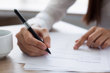 questionary: Closeup of Woman Completing Application Form Stock Photo
