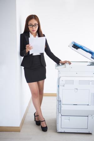 Serious Asian Woman at Multifunction Printer