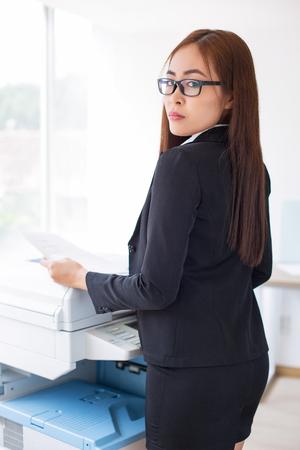 fotocopiadora: Serious Business Lady Using Photocopier in Office Foto de archivo