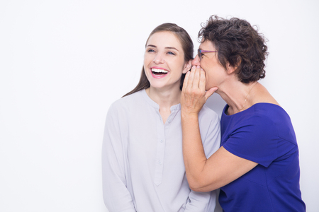 Senior woman whispering secret to cheerful woman
