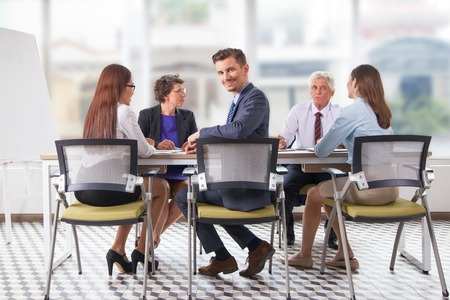 Smiling businessman sitting at meeting with team Stock Photo