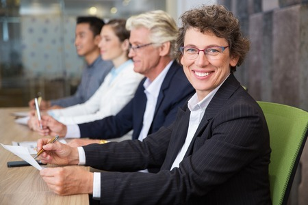 Cheerful senior businesswoman sitting at meeting
