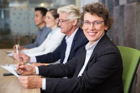 Vrolijke senior zaken vrouw zitten op vergadering