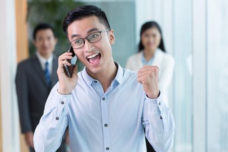 Gelukkige zakenman die op telefoon en het schreeuwen spreekt