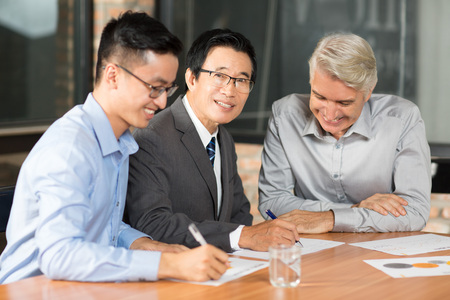 cerrando negocio: Smiling Asian business people closing deal