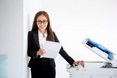 Positive young businesswoman standing at printer