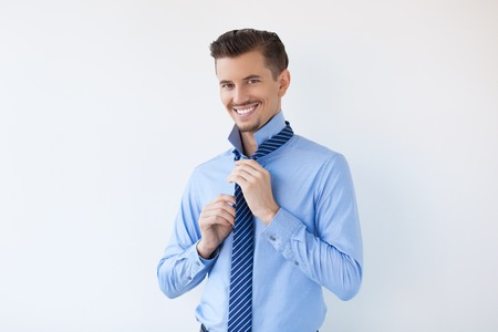Closeup of Smiling Attractive Man Tying Necktie Stock Photo