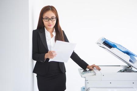 Content Aziatische vrouwelijke assistent die zich bij Copier