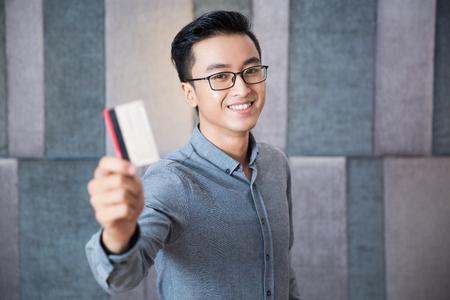 Vrolijke Aziatische mens die creditcard tonen aan camera Stockfoto