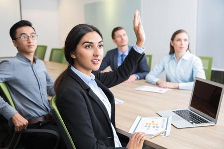 Zekere jonge manager verhoging van de hand op workshop