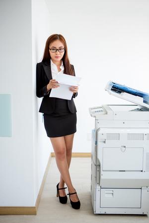 Confident Asian businesswoman standing at printer
