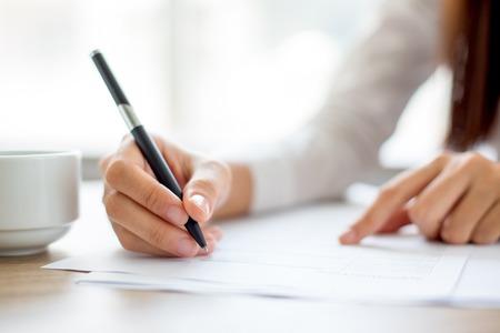 Hand van onderneemster die op papier in bureau schrijft