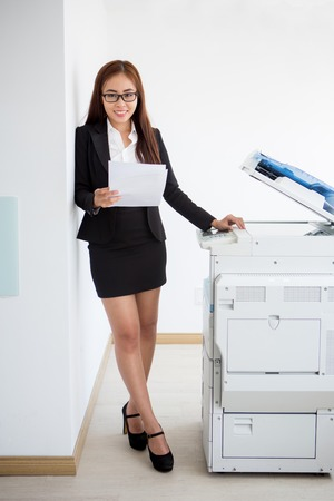 Portrait of smiling young businesswoman at copier