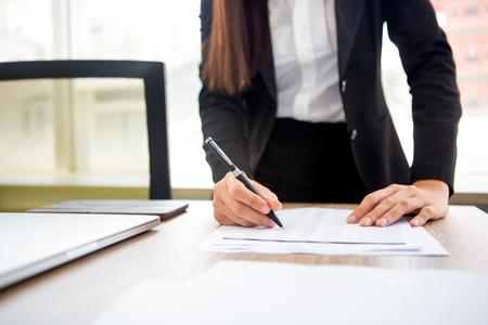 Jonge zakenvrouw schrijven op papier in kantoor