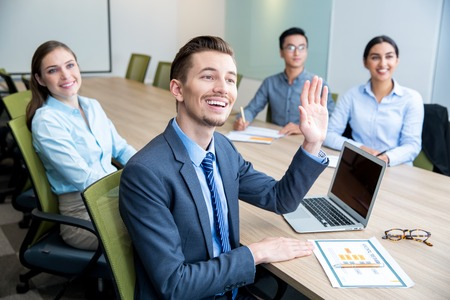 Glimlachende bedrijfsmens die hand op conferentie opheft Stockfoto