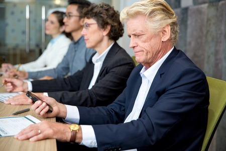 Serious senior businessman sitting at meeting