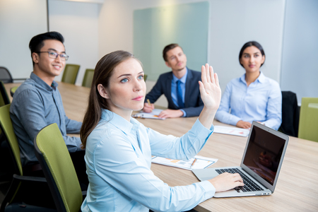 Business Woman Raising Hand at Conference
