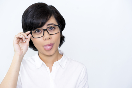 Cheerful businesswoman in glasses showing tongue