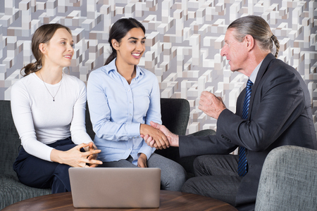 sealing: Agent and Women Couple Sealing Deal with Handshake Stock Photo