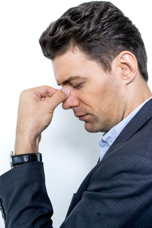 overworking: Portrait of tired young businessman rubbing eyes