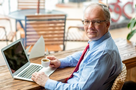 mature business man: Content Business Man Working in Cafe with Coffee