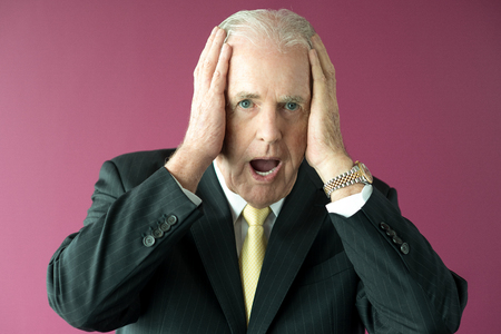 Shocked Senior Business Man Clutching Head