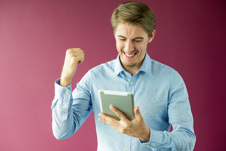 Happy businessman with touchpad gesturing success
