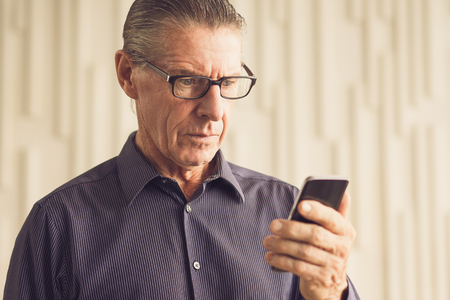 phone professional: Worried Senior Man Reading Text Message on Phone