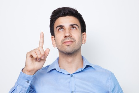 Serious Young Handsome Man Pointing Upwards Stock Photo